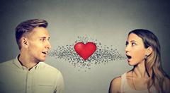 Love connection. Man woman talking to each other red heart in-between Stock Photos