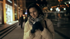 Woman walking in city at night time with cup of coffee Stock Footage
