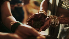 Woman puts green grains in bride's palms Stock Footage