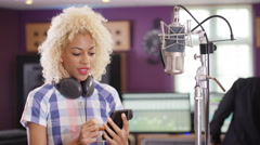 4K Female vocalist in recording studio using mobile phone for video call Stock Footage