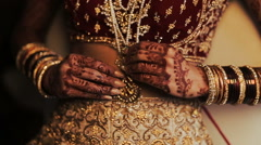 Indian bride's long finders hold a golden pendant hanging over her red costume Stock Footage