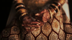 Closeup of Indian bride's hands covered with mehndi and holding a golden Stock Footage