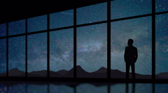 Businessman stand at the panoramic window on background starry sky.Time lapse Stock Footage