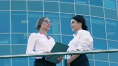 Two friendly female coworkers doing business outdoors Stock Footage