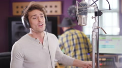4K Male vocalist in recording studio singing into mic Stock Footage