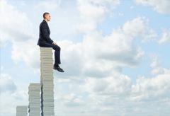 Businessman sitting on top pile of stocks Stock Photos