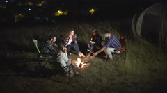 The people on camping near the fire the background on the city. Crane shot Stock Footage