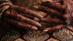 Bride's arms pained with mehndi lie on her red dress with golden design Stock Footage