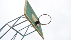 Old basketball hoop outdoors rusty iron sport ball enters the basket Stock Footage
