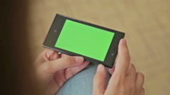 Pretty woman holding in hand smart phone with green screen display Stock Footage