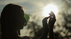 Silhouette of woman with smart phone at sunset Stock Footage