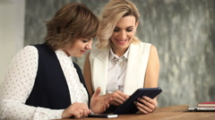 Female friends sitting in office laughing and looking at digital tablet Arkistovideo