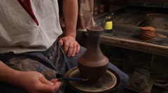 Adult male potter master creating new ceramic pot on pottery wheel. Front view Stock Footage
