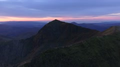 Aerial view up and over Crib Goch with views of the summit of Snowdon. Stock Footage