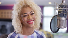 4K Portrait smiling female vocalist in recording studio standing at microphone Stock Footage