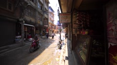 Walking along the street in Thamel, Kathmandu. Worker pours water on pavement Stock Footage