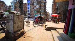 View of rickshaws' cycles and monks walking towards. Thamel district, Kathmandu Stock Footage