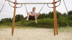 Beautiful little girl on a swing Baltic Sea Stock Footage