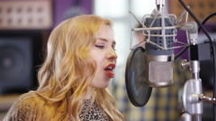 4K Portrait smiling female vocalist in recording studio singing into microphone. Stock Footage