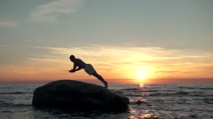 Man silhouette doing push-ups at the beach Stock Footage