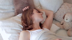 Portrait of sleeping young woman, she wakes up and looks at light from window Stock Footage