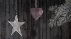 Christmas toys hanging on a branch of a Christmas tree on a wooden background. Stock Footage