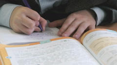 Schoolboy writes the text in the copybook indoors Stock Footage
