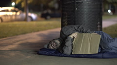 Homeless man startled while sleeping on sidewalk at night Stock Footage