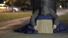Man hiding face with blank cardboard sign outdoors at night 4k Stock Footage