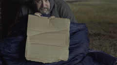 Homeless man with cardboard sign looking at camera 4k Stock Footage