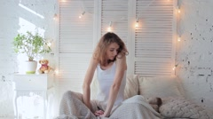 Morning young beautiful woman, she stretches sitting cross-legged on bed Stock Footage