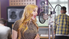 4K Female vocalist in recording studio singing into mic Stock Footage