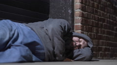 Man sleeping in cold city back streets at night 4k Stock Footage