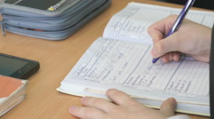 Schoolgirl writes the text in the school diary Stock Footage