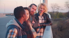 Four friends hanging out on bridge Stock Footage
