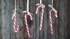 Candy Canes hanging on a ribbon a wooden background. Stock Footage
