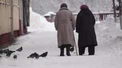 Two old women slowly walking along the sidewalk in winter Stock Footage