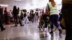 Dissabled person in wheelchair going to the Queue of a Gate in an Airport. Stock Footage