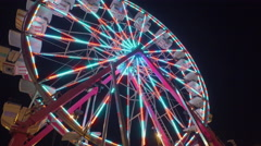 Fall Fair  Medium wide shot looking up at Ferris Wheel flashing in the night Stock Footage