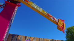 Fall Fair Medium shot follows long ride as it swings people up into the air Stock Footage