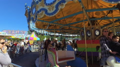 Fall Fair Medium shot pans along with merry-go-round as kids an adults ride it Stock Footage