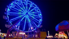 Fall Fair Static wide shot of ferris wheel spinning and people walking around Stock Footage