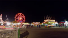 Fall Fair Wide shot walking along fair grounds at night with rides and people Stock Footage