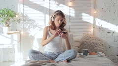 Happy woman in headphones listening to music from smartphone and dancing in bed Stock Footage