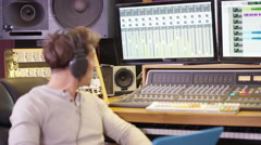 4K Young sound engineer in recording studio using laptop at the mixing desk Stock Footage