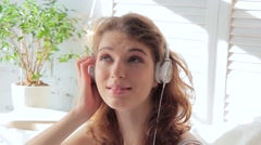 Young smiling woman listening to music with headphones on a sunny morning Stock Footage