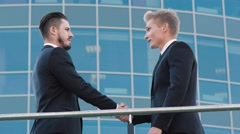 Two confident business men meeting outdoors at the place which they are going to Stock Footage