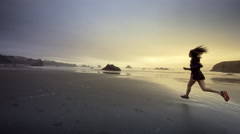 Young woman running on Pacific Ocean beach at sunset. Stock Footage