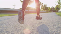 SLOW MOTION CLOSE UP: Young woman jogging in beautiful tree avenue in evening Stock Footage