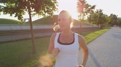 SLOW MOTION CLOSE UP: Pretty female jogging in amazing tree avenue in evening Stock Footage